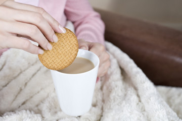 A woman dipping a biscuit in a cup of tea