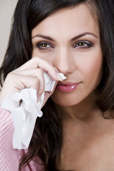 A young woman wiping her nose with a tissue, close-up