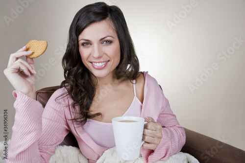 A young woman holding a cup of tea and a biscuit