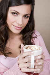 A young woman holding a cup of hot chocolate