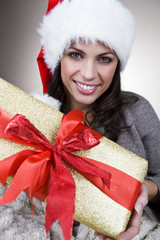 A young woman wearing a Santa hat, holding a Christmas present
