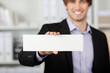 mann im büro zeigt weißes schild