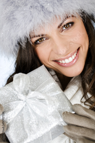 A young woman holding a Christmas present