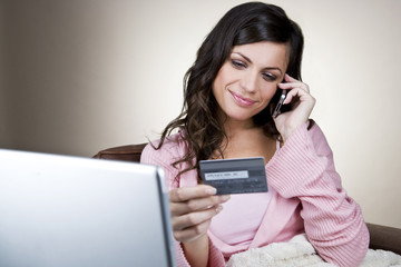 A young woman on the phone, holding her credit card