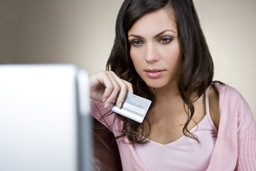 A young woman holding a credit card and using a laptop