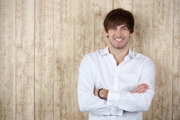 lächelnder mann mit verschränkten armen