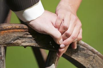 Hochzeitspaar halten sich die Hände auf einem alten Holzrad