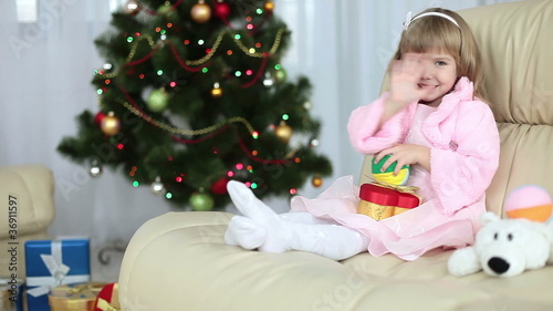 Happy little girl with toys on the couch next to Christmas tree