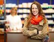 Frau mit verschränkten Armen in Apotheke