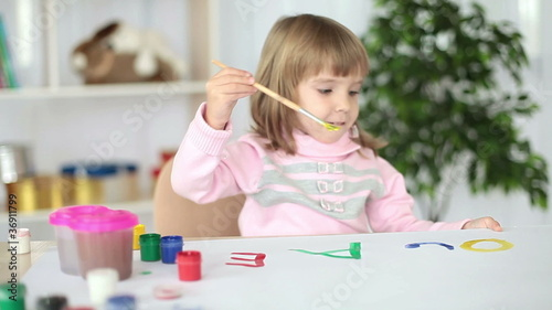 Girl paints letters of the alphabet
