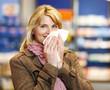 Frau mit Taschentuch in Apotheke