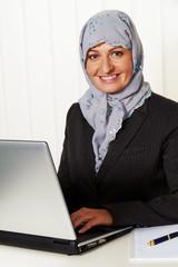 Frau mit Kopftuch im Büro