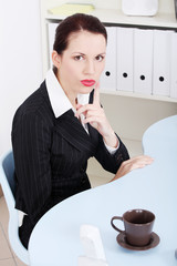 Businesswoman showing silence sign