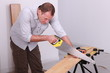Man sawing a wooden floor