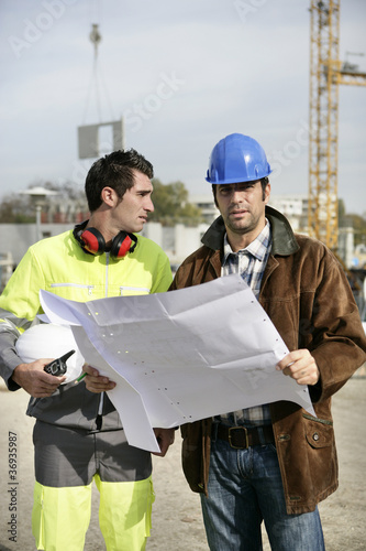 Construction workers looking at site plans