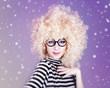 Portrait of funny girl in blonde wig.