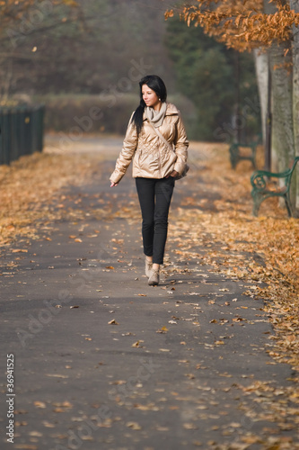 pretty young woman walking in autumn park