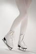 Woman's Legs in White Ice Skates