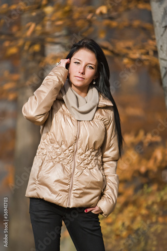 portrait of pretty young woman in autumn park