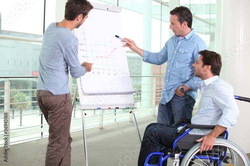 Man in wheelchair with colleagues