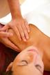 Schultermassage einer schönen Frau - Fokus auf den Händen