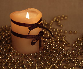 Burning yellow candle in a gold decoration
