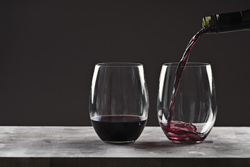Pouring Red Wine into Glass against Brown Background