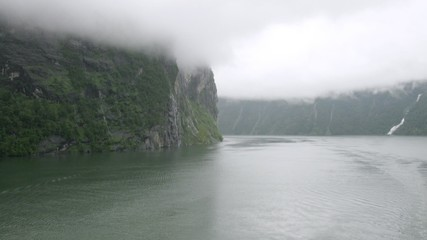 Dark fjord covered with white fog, view from ship, time lapse