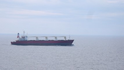 Lonely freight ship in open sea in cloudy weather