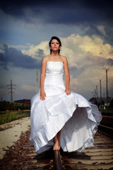 Beautiful young brunette bride is walking on the railway