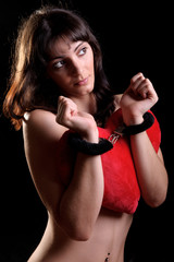sensual woman wearing handcuffs holding a heart shaped pillow