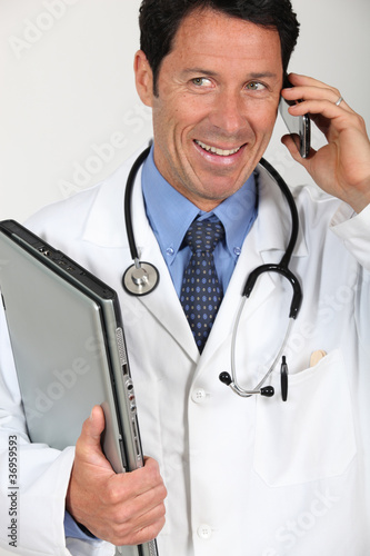 A doctor holding a laptop and having a conversation