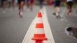 Big orange cone on road between running people, close-up view