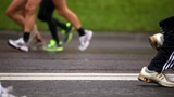 Pair of man legs run in jogging shoes on wet asphalt
