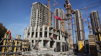 Workers lift valve using a high crane on construction site