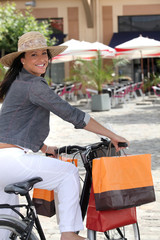 a woman riding a bike after the shopping