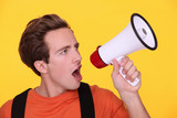 Young man hollering into a megaphone