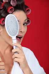 Woman with hair curlers holding a brush