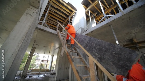 Two workers carry huge plate by wooden stairs to second storey