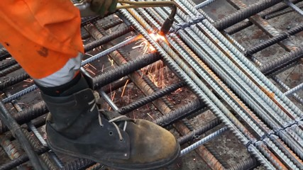 Worker legs in orange clothes weld metal grating