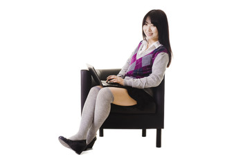 Chinese student working on a laptop and sitting in a chair.