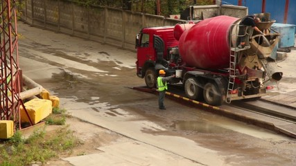 Two workers wash concrete mixer