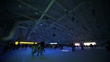 Many people skate on ice rink with colored illumination