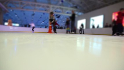 People skate on ice rink with colored illumination