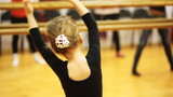 girl repeats movement elbows of adults dancers standing