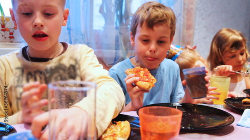 children sit around table, celebrating birthday party