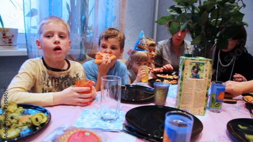 family and children sit around table, celebrating birthday party