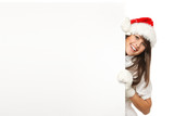 Girl wearing Santa hat pulling out a blank billboard