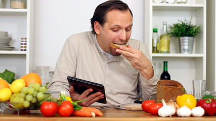 Man in kitchen with electronic tablet eat breakfast