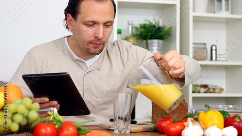 Man in kitchen with electronic tablet drink juice